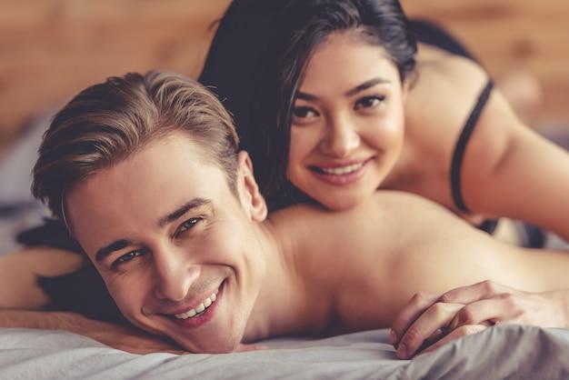 La bella giovane coppia sta esaminando la macchina fotografica e sorridere.