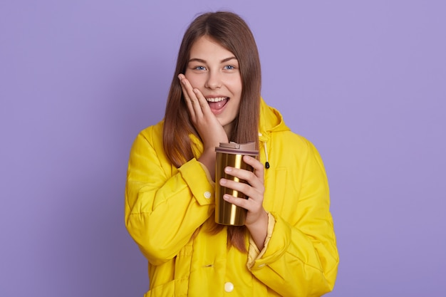 La bella giovane donna adorabile che tiene la termo tazza di tè e che tiene la palma sulla guancia, tiene la bocca aperta, sembra eccitata, il maglione giallo d'uso, posante isolato sopra la parete lilla.