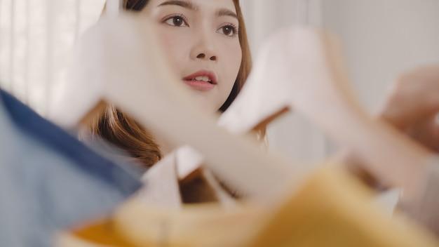 La bella giovane donna asiatica attraente che sceglie la sua attrezzatura di modo copre in gabinetto a casa
