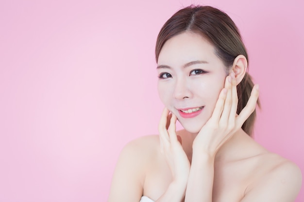 La bella giovane donna asiatica caucasica tocca il suo fronte pulito della pelle fresca. cosmetologia, cura della pelle, pulizia della faccia