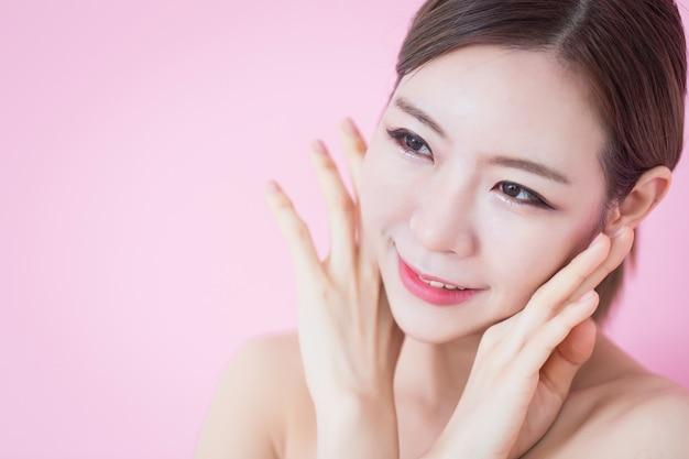 La bella giovane donna asiatica caucasica tocca il suo fronte pulito della pelle fresca