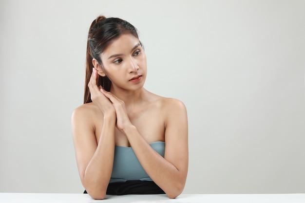 La bella giovane donna asiatica con pelle pulita fresca distoglie lo sguardo. cura della bellezza della ragazza. trattamento facciale .