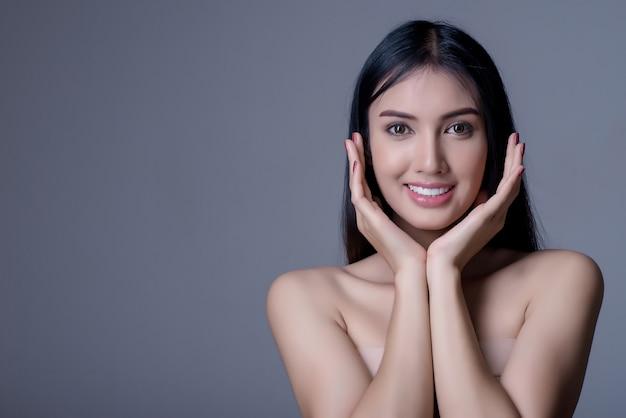 La bella giovane donna asiatica con pelle pulita fresca tocca il proprio fronte, bellezza e stazione termale.