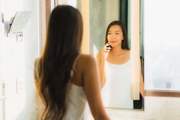 La bella giovane donna asiatica controlla il suo fronte in bagno