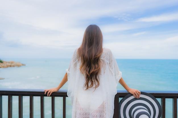 La bella giovane donna asiatica del ritratto che guarda l'oceano della spiaggia del mare per si rilassa nel viaggio di vacanza di festa