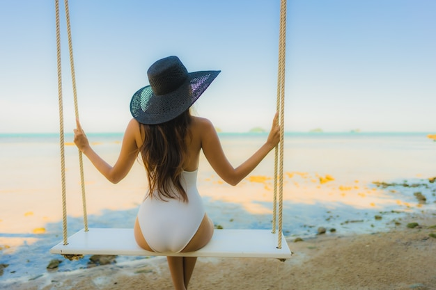 La bella giovane donna asiatica del ritratto che si siede sull'oscillazione intorno all'oceano del mare della spiaggia per si rilassa