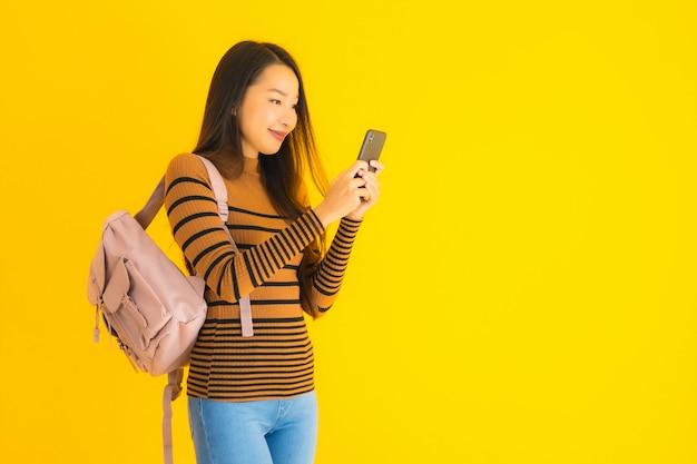 La bella giovane donna asiatica del ritratto con il bagpack utilizza lo smartphone