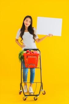 La bella giovane donna asiatica del ritratto con il carretto del cestino della drogheria e mostra il bordo vuoto bianco