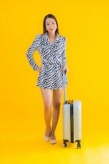 La bella giovane donna asiatica del ritratto con il passaporto e l'imbarco dei bagagli di viaggio passa il giallo