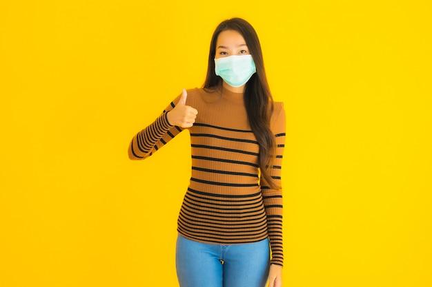 La bella giovane donna asiatica del ritratto con la maschera in molte azioni per protegge da coronavirus o covid19