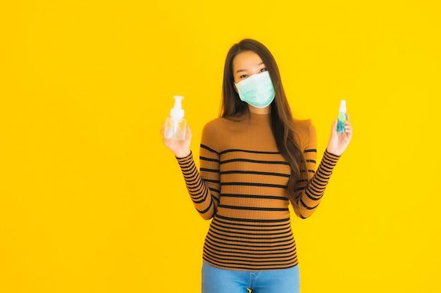La bella giovane donna asiatica del ritratto con lo spruzzo dell'alcool della maschera e il gel imbottigliano la sua mano per proteggono da coronavirus o covid19