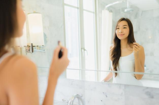La bella giovane donna asiatica del ritratto controlla e compone il suo fronte