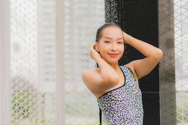 La bella giovane donna asiatica del ritratto fa una doccia intorno alla piscina all'aperto