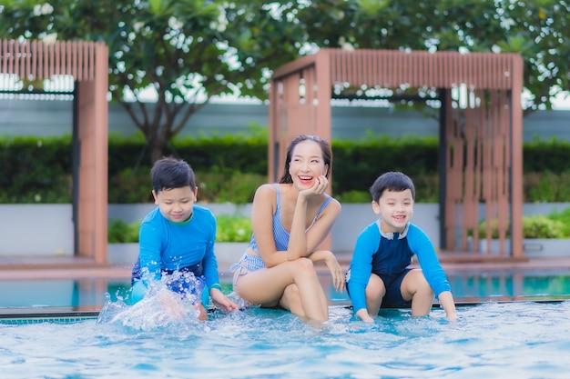 La bella giovane donna asiatica del ritratto gode del relax felice con il figlio intorno alla piscina