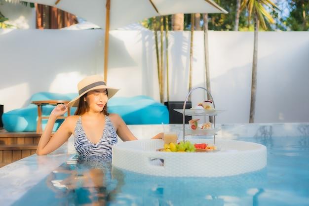 La bella giovane donna asiatica del ritratto gode di con il tè o la prima colazione di pomeriggio che galleggia sulla piscina