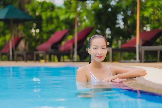 La bella giovane donna asiatica del ritratto gode di relax sorriso svago intorno alla piscina all'aperto in hotel