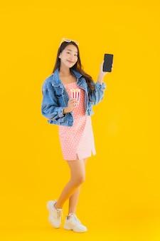 La bella giovane donna asiatica del ritratto gode di soddisfatto del popcorn del telefono e guarda il film