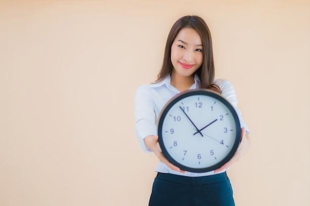 La bella giovane donna asiatica del ritratto mostra la sveglia o l'orologio