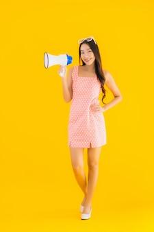 La bella giovane donna asiatica del ritratto parla forte con il megafono