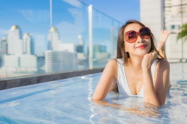 La bella giovane donna asiatica del ritratto rilassa lo svago intorno alla piscina