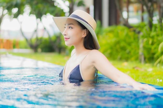 La bella giovane donna asiatica del ritratto si rilassa gode del sorriso intorno alla piscina all'aperto nella località di soggiorno dell'hotel sulla vacanza di svago