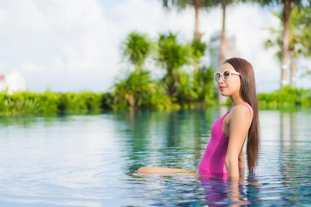 La bella giovane donna asiatica del ritratto si rilassa gode intorno alla piscina all'aperto nella vacanza di festa