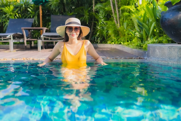 La bella giovane donna asiatica del ritratto si rilassa il sorriso felice intorno alla piscina all'aperto nella località di soggiorno dell'hotel per le vacanze di svago