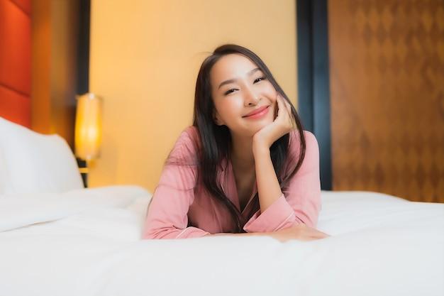 La bella giovane donna asiatica del ritratto si rilassa il sorriso felice sul letto nell'interno della camera da letto