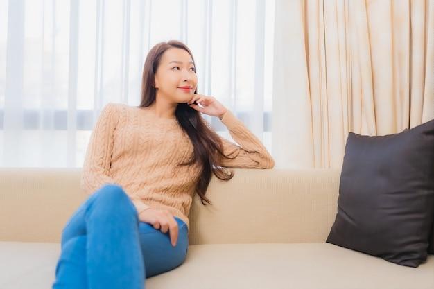 La bella giovane donna asiatica del ritratto si rilassa il sorriso felice sull'interno della decorazione del sofà della camera da letto