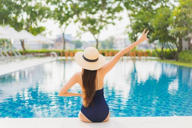 La bella giovane donna asiatica del ritratto si rilassa il sorriso intorno alla piscina all'aperto nella località di soggiorno dell'hotel sul viaggio di vacanza