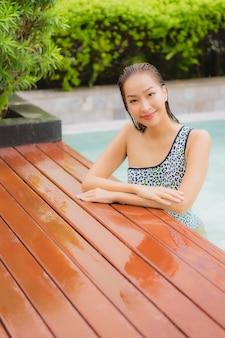 La bella giovane donna asiatica del ritratto si rilassa il sorriso intorno alla piscina all'aperto per il tempo libero e le vacanze