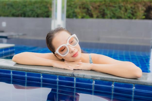 La bella giovane donna asiatica del ritratto si rilassa il sorriso intorno alla piscina all'aperto
