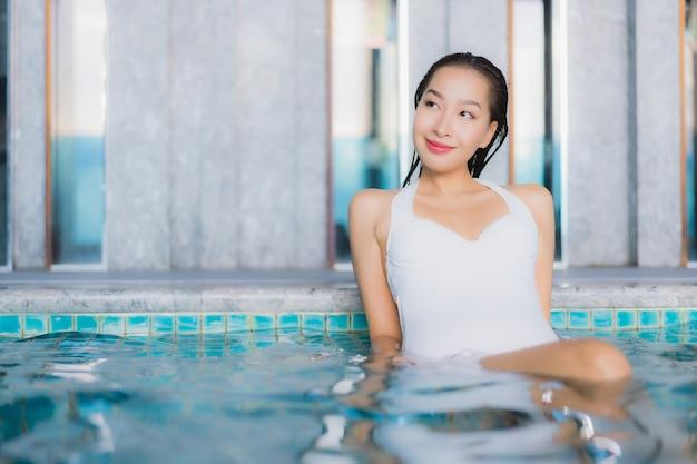La bella giovane donna asiatica del ritratto si rilassa il sorriso intorno alla piscina nella località di soggiorno dell'hotel sulla vacanza di traval