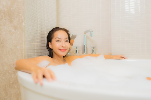 La bella giovane donna asiatica del ritratto si rilassa il sorriso nella vasca da bagno all'interno del bagno
