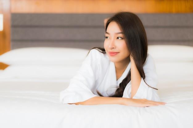 La bella giovane donna asiatica del ritratto si rilassa il sorriso sul letto nell'interno della camera da letto
