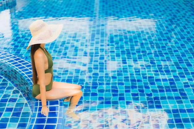 La bella giovane donna asiatica del ritratto si rilassa intorno alla piscina nella località di soggiorno dell'hotel
