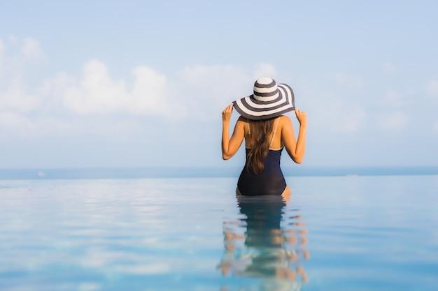 La bella giovane donna asiatica del ritratto si rilassa intorno alla piscina