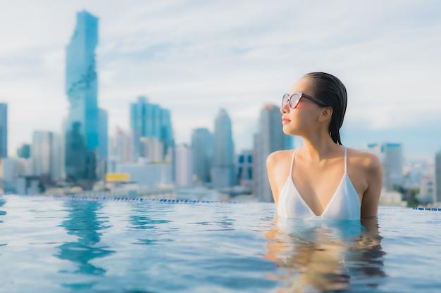 La bella giovane donna asiatica del ritratto si rilassa lo svago felice di sorriso intorno alla piscina all'aperto