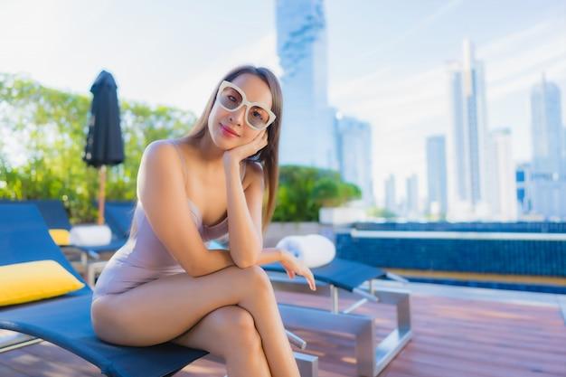 La bella giovane donna asiatica del ritratto si rilassa lo svago gode di intorno alla piscina all'aperto