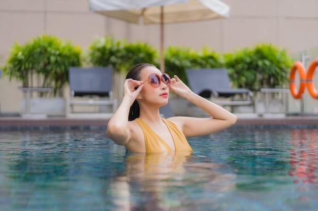 La bella giovane donna asiatica del ritratto si rilassa lo svago intorno alla piscina