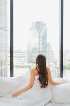 La bella giovane donna asiatica del ritratto si rilassa lo svago sul letto con la vista della città
