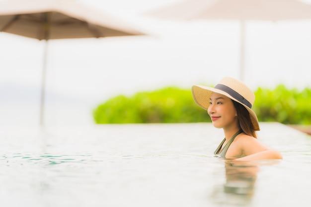 La bella giovane donna asiatica del ritratto si rilassa nella piscina all'aperto di lusso nell'oceano quasi del mare della spiaggia della località di soggiorno dell'hotel