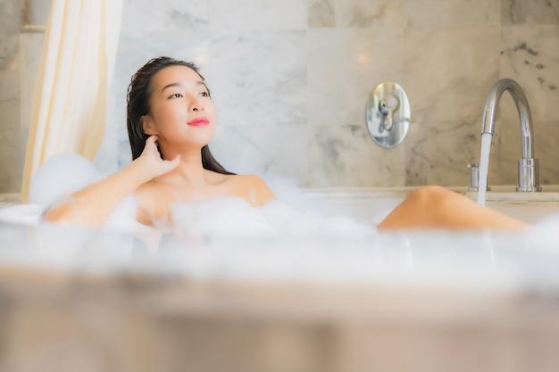 La bella giovane donna asiatica del ritratto si rilassa prende un bagno