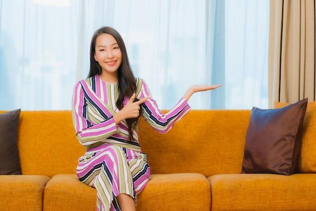 La bella giovane donna asiatica del ritratto si rilassa sul sofà nell'interno del salone