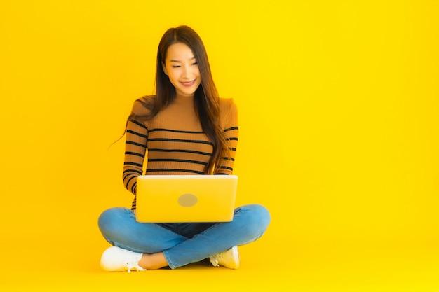 La bella giovane donna asiatica del ritratto si siede sul pavimento per il computer portatile o il computer di uso sulla parete gialla