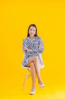 La bella giovane donna asiatica del ritratto si siede sulla sedia con azione su giallo