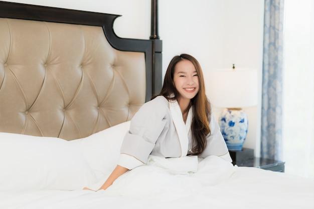 La bella giovane donna asiatica del ritratto sveglia con felice e sorride sul letto nell'interno della camera da letto