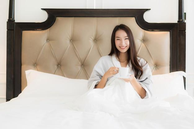 La bella giovane donna asiatica del ritratto sveglia con il sorriso felice e la tazza di caffè sul letto in camera da letto inter