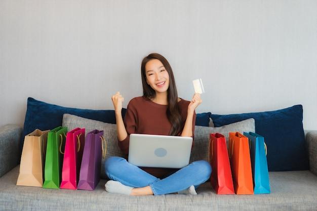 La bella giovane donna asiatica del ritratto utilizza il computer portatile e la carta di credito per lo shopping online sul divano nell'interno del soggiorno