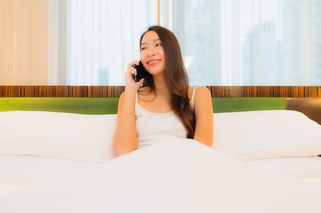 La bella giovane donna asiatica del ritratto utilizza il telefono cellulare astuto sul letto nell'interno della camera da letto